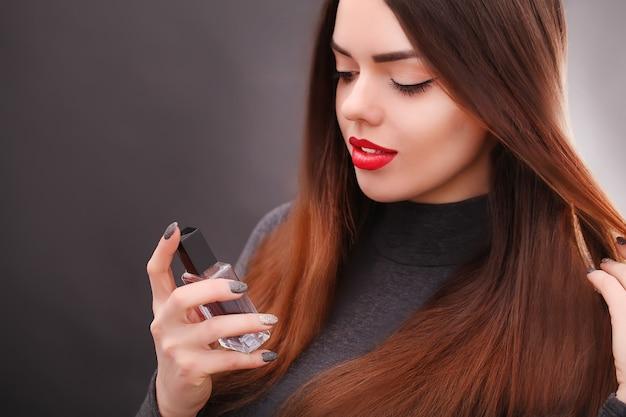 Młoda azjatycka seksowna kobieta o ciemnych włosach za pomocą czerwonej szminki
