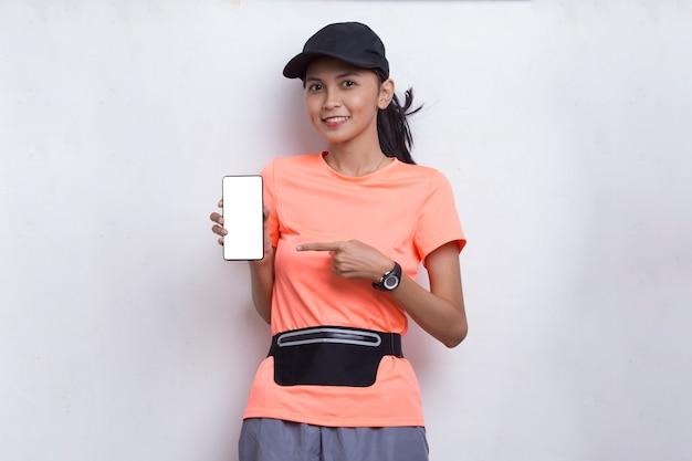 Młoda azjatycka sportowa kobieta demonstruje telefon komórkowy na białym tle