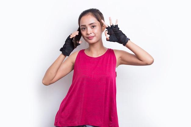 Młoda azjatycka sportowa kobieta korzystająca z telefonu komórkowego na białym tle