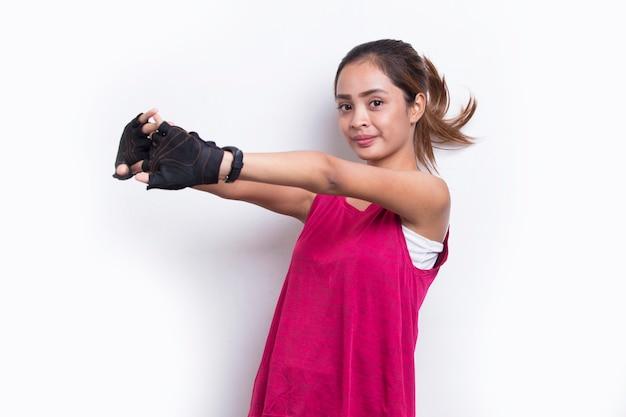 Młoda azjatycka sportowa kobieta robi rozciąganie na białym tle