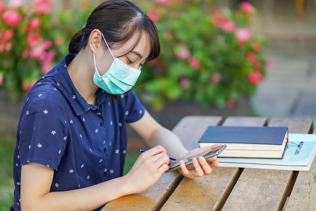 Młoda azjatycka studencka kobieta jest ubranym medyczną maskę i trzyma smartphone, patrzeje ekran, używa app lub przesyłanie wiadomości, podczas gdy siedzący przy ogrodową ławką z książką. nowa normalna koncepcja po covid-19