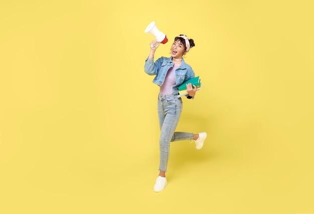 Młoda azjatycka studentka krzyczy do megafonu co ogłoszenie w na białym tle na żółtym tle.