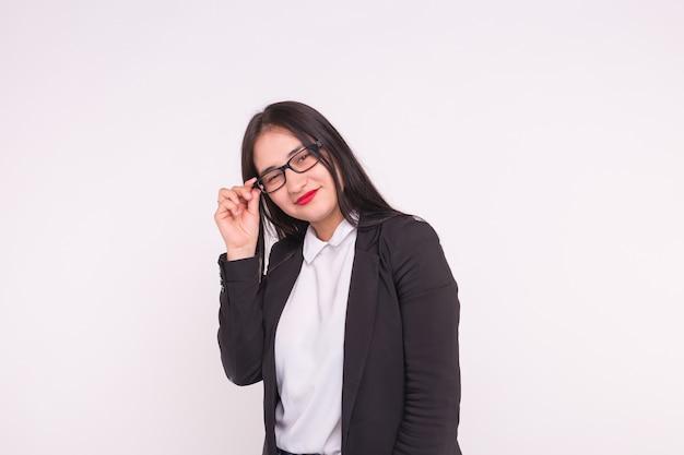 Młoda azjatycka studentka lub biznesowa dama w okularach na białym tle.