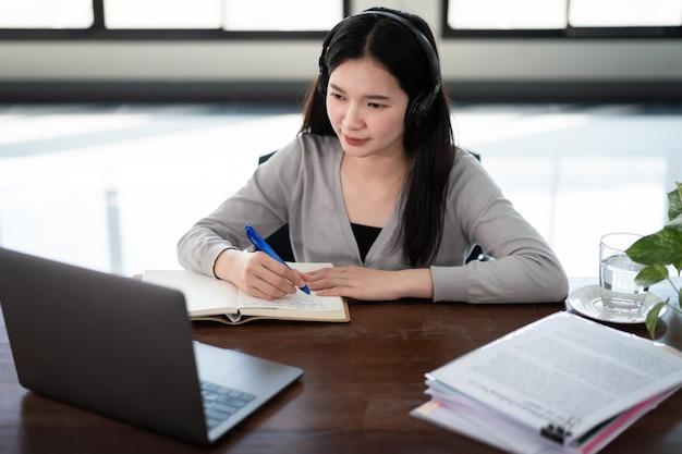 Młoda azjatycka studentka nosi bezprzewodowe słuchawki pisz na notebooku, aby uczyć się języka online, oglądaj i słuchaj wykładowcy, seminarium internetowe za pośrednictwem połączenia wideo e-learning w domu, edukacja na odległość