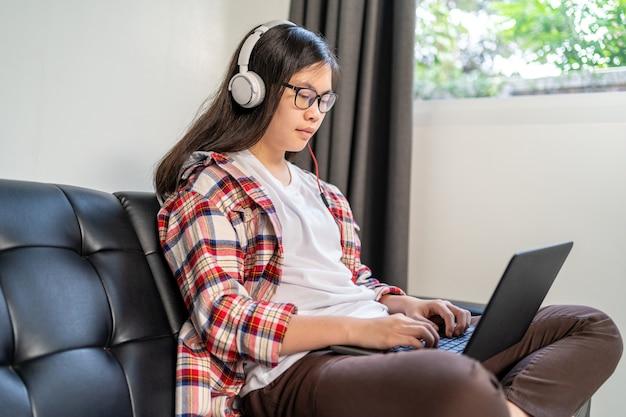 Młoda azjatycka studentka pracująca i ucząca się w domu podczas blokady miasta z powodu rozprzestrzeniania się wirusa koronowego