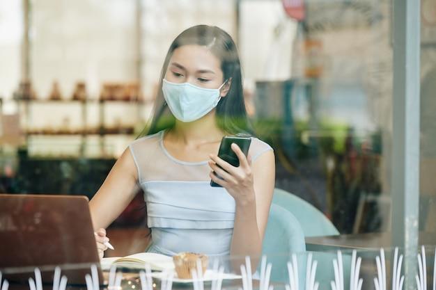 Młoda azjatycka studentka w masce ochronnej pracuje na laptopie w kafeterii kolegium