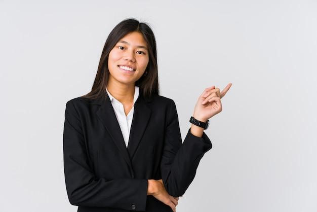 Młoda azjatykcia biznesowa kobieta ono uśmiecha się radośnie wskazujący z palcem wskazującym daleko od.