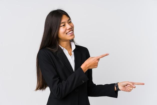 Młoda azjatykcia biznesowa kobieta podekscytowany wskazuje z palcami wskazującymi daleko od.