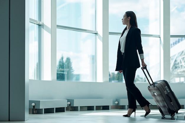 Młoda azjatykcia biznesowa kobieta w lotnisku z bagażową tramwaj torbą, czeka odjazd