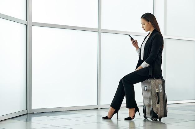 Młoda azjatykcia biznesowa kobieta w lotnisku z bagażową tramwaj torbą, opowiada na telefonie i ono uśmiecha się.