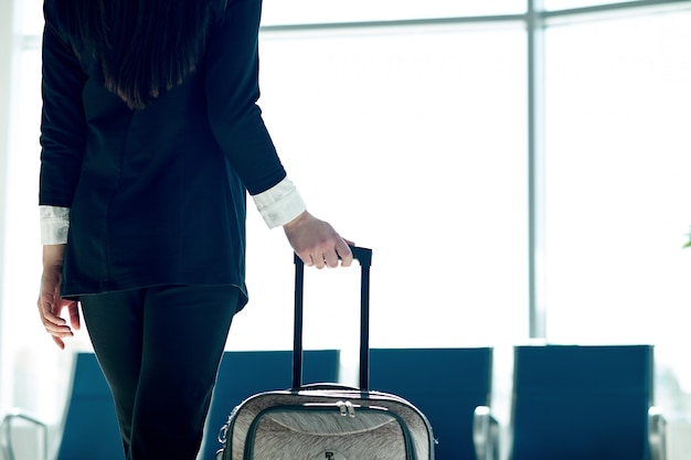 Młoda azjatykcia biznesowa kobieta w lotnisku z tramwaj torbą, czeka odjazd