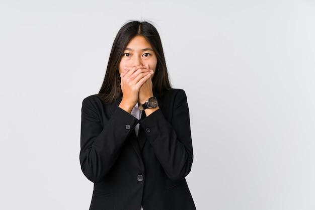 Młoda azjatykcia biznesowa kobieta zszokował nakrywkowego usta z rękami.