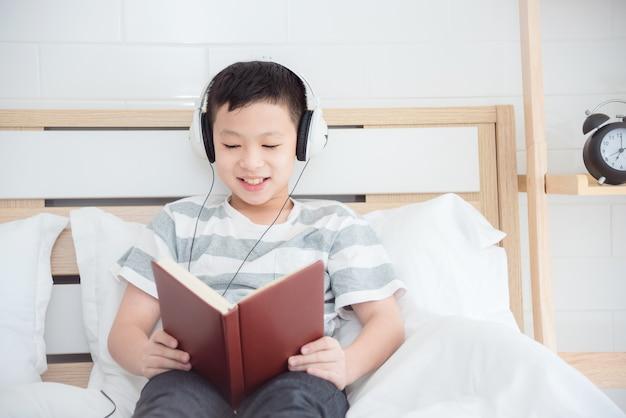 Młoda azjatykcia chłopiec jest ubranym słuchawki i czytelniczą książkę na łóżku