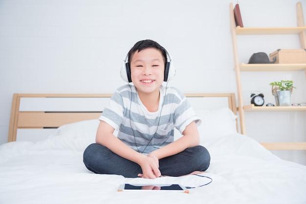 Młoda azjatykcia chłopiec jest ubranym słuchawki słuchającą muzykę