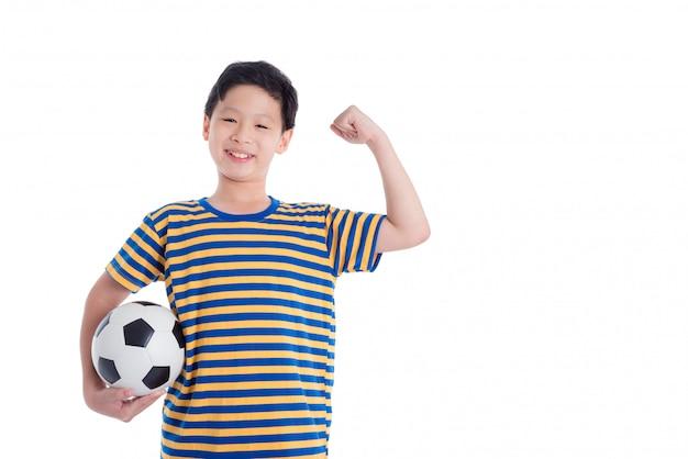 Młoda azjatykcia chłopiec mienia piłka i uśmiechy nad białym tłem