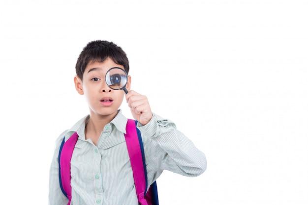 Młoda azjatykcia chłopiec patrzeje przez lupy nad białym tłem