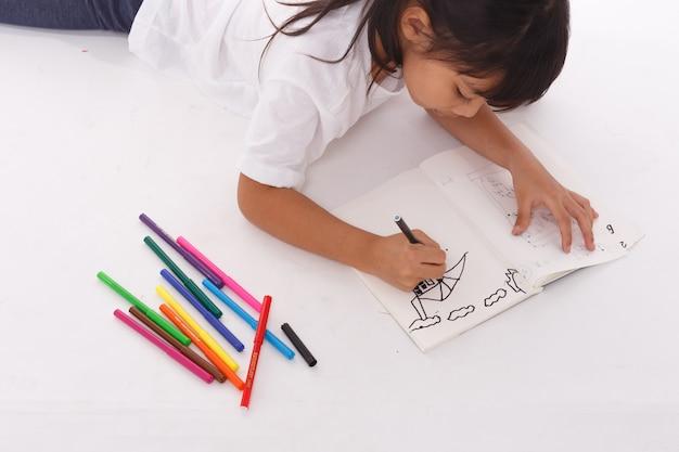 Młoda azjatykcia dziewczyna rysuje obrazek. na białym