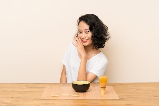 Młoda azjatykcia dziewczyna szepcze coś z herbacianą matcha
