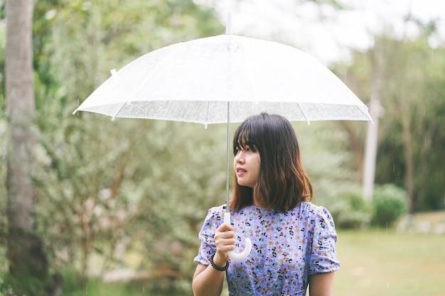 Młoda azjatykcia dziewczyna w deszczu z parasolem.