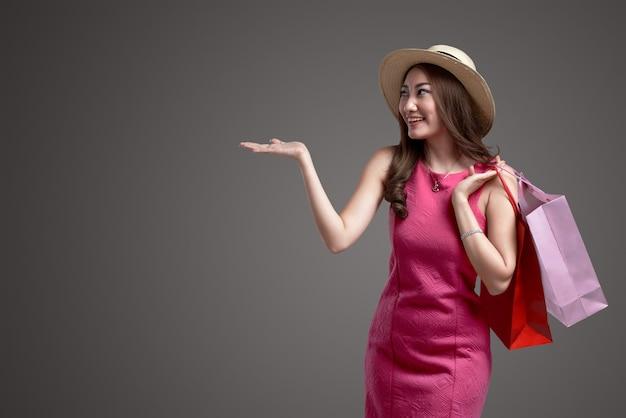 Młoda azjatykcia dziewczyna z kapeluszowymi mień torba na zakupy
