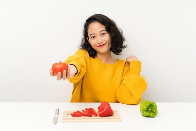 Młoda azjatykcia dziewczyna z warzywami w stole