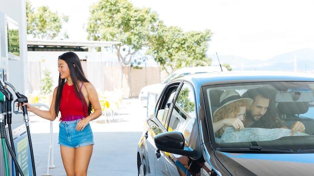 Młoda azjatykcia kobieta bierze dyszową pompę paliwa podczas gdy przyjaciele bada mapę