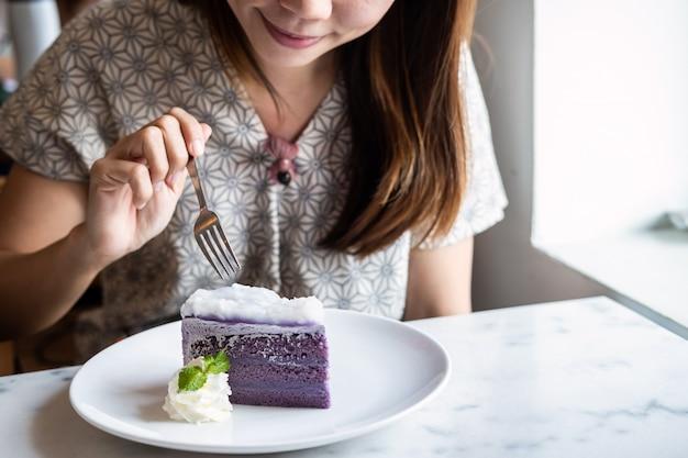 Młoda azjatykcia kobieta cieszy się łasowanie deser w restauraci