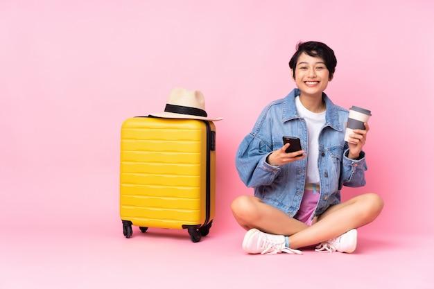 Młoda azjatykcia kobieta iść podróżować nad odosobnionym tłem