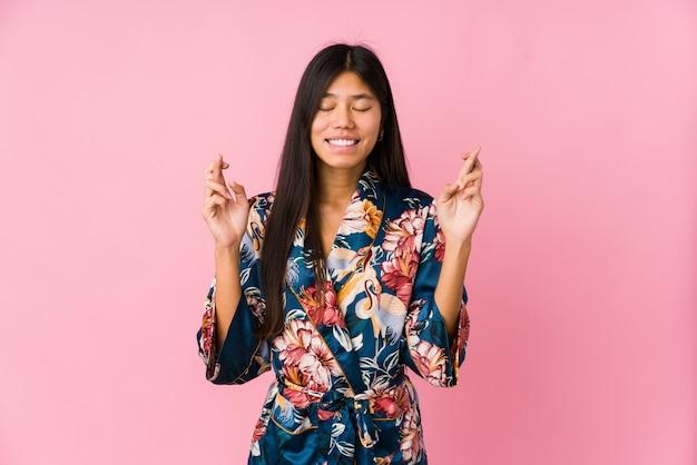 Młoda azjatykcia kobieta jest ubranym kimonową piżamę krzyżuje palce dla mieć szczęście