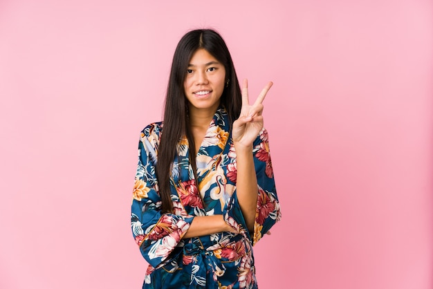 Młoda azjatykcia kobieta jest ubranym kimonową piżamę pokazuje numer dwa z palcami.