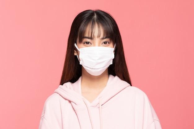Młoda azjatykcia kobieta jest ubranym ochrony maskę lub chirurgicznie maskę dla ochraniającego wirusa i zanieczyszczenia powietrza na menchii ścianie, opiece zdrowotnej i coronavirus pojęciu ,.
