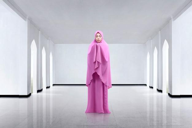 Młoda azjatykcia kobieta jest ubranym przesłonę i ono modli się
