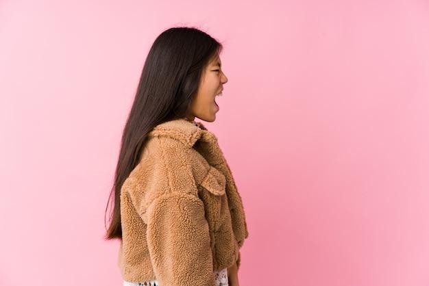 Młoda azjatykcia kobieta krzyczy w kierunku odbitkowej przestrzeni