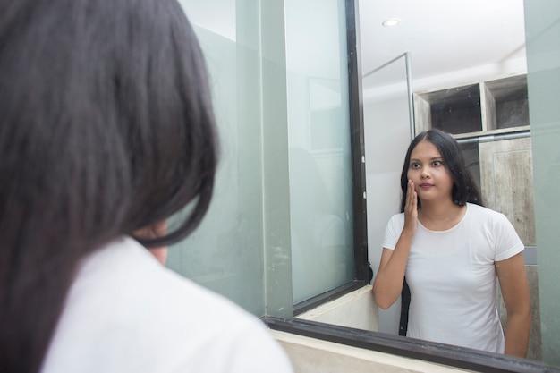Młoda azjatykcia kobieta mycia twarzy w pokoju