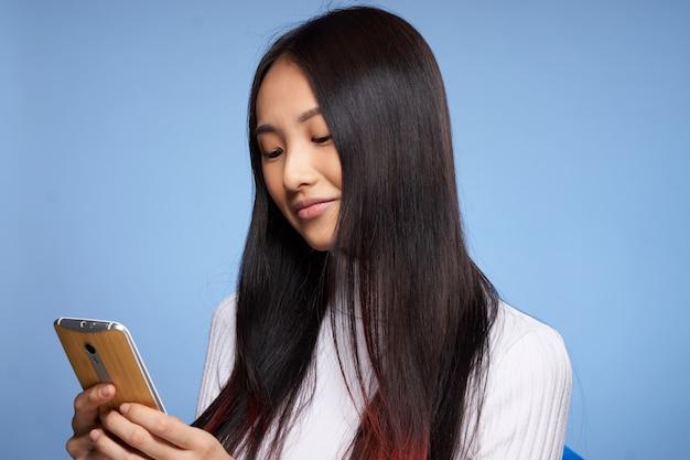 Młoda azjatykcia kobieta na błękitnej ściany pozować, różne emocje, wyśmiewa up
