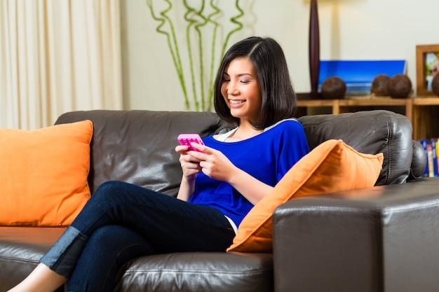 Młoda azjatykcia kobieta na kanapie w domu