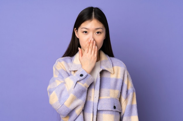 Młoda azjatykcia kobieta na purpurach izoluje nakrywkowego usta z ręką