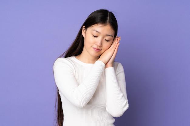 Młoda azjatykcia kobieta na purpurach ścienny robi sen gestowi w dorable wyrażeniu