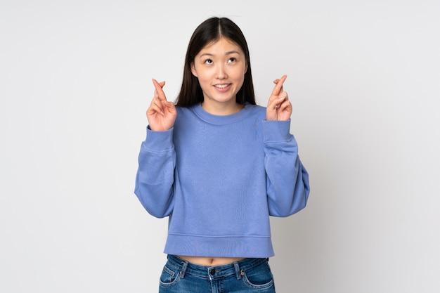 Młoda azjatykcia kobieta na ścianie z palcami krzyżuje best i życzy