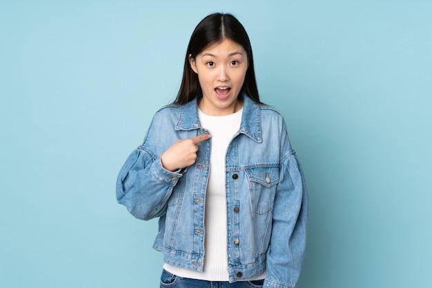 Młoda azjatykcia kobieta na ścianie z zdziwionym wyrazem twarzy