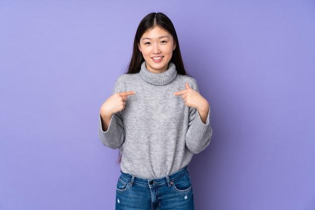 Młoda azjatykcia kobieta nad ścianą z zdziwionym wyrazem twarzy