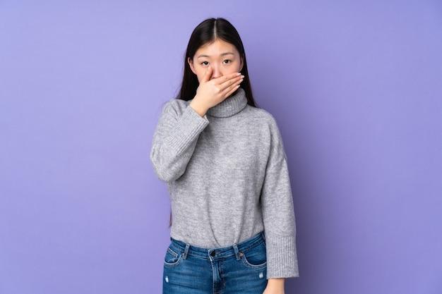 Młoda azjatykcia kobieta nad ściennym nakrywkowym usta z ręką
