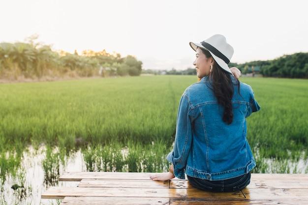 Młoda azjatykcia kobieta ono uśmiecha się w kapeluszu. dziewczyna cieszy się przy piękną naturą z zmierzchem.