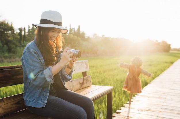 Młoda azjatykcia kobieta ono uśmiecha się w kapeluszu. dziewczyna używa kamerę i cieszy się przy piękną naturą.