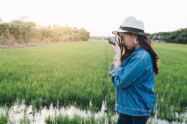 Młoda azjatykcia kobieta ono uśmiecha się w kapeluszu. dziewczyna używa kamerę i cieszy się przy piękną naturą