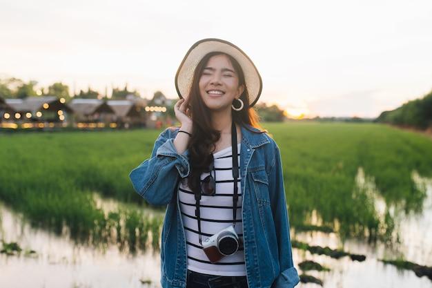 Młoda azjatykcia kobieta ono uśmiecha się w kapeluszu z kamerą. dziewczyna cieszy się przy piękną naturą z sunse