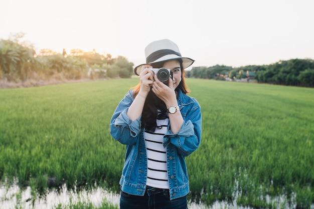 Młoda azjatykcia kobieta ono uśmiecha się w kapeluszu z kamerą. dziewczyna cieszy się przy piękną naturą z zmierzchem.