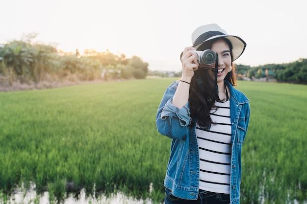 Młoda azjatykcia kobieta ono uśmiecha się w kapeluszu z kamerą. dziewczyna cieszy się przy piękną naturą.