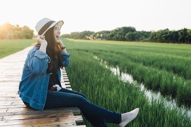 Młoda azjatykcia kobieta ono uśmiecha się w kapeluszu.