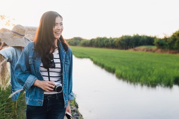 Młoda azjatykcia kobieta ono uśmiecha się z kamerą. dziewczyna cieszy się przy piękną naturą z zmierzchem.